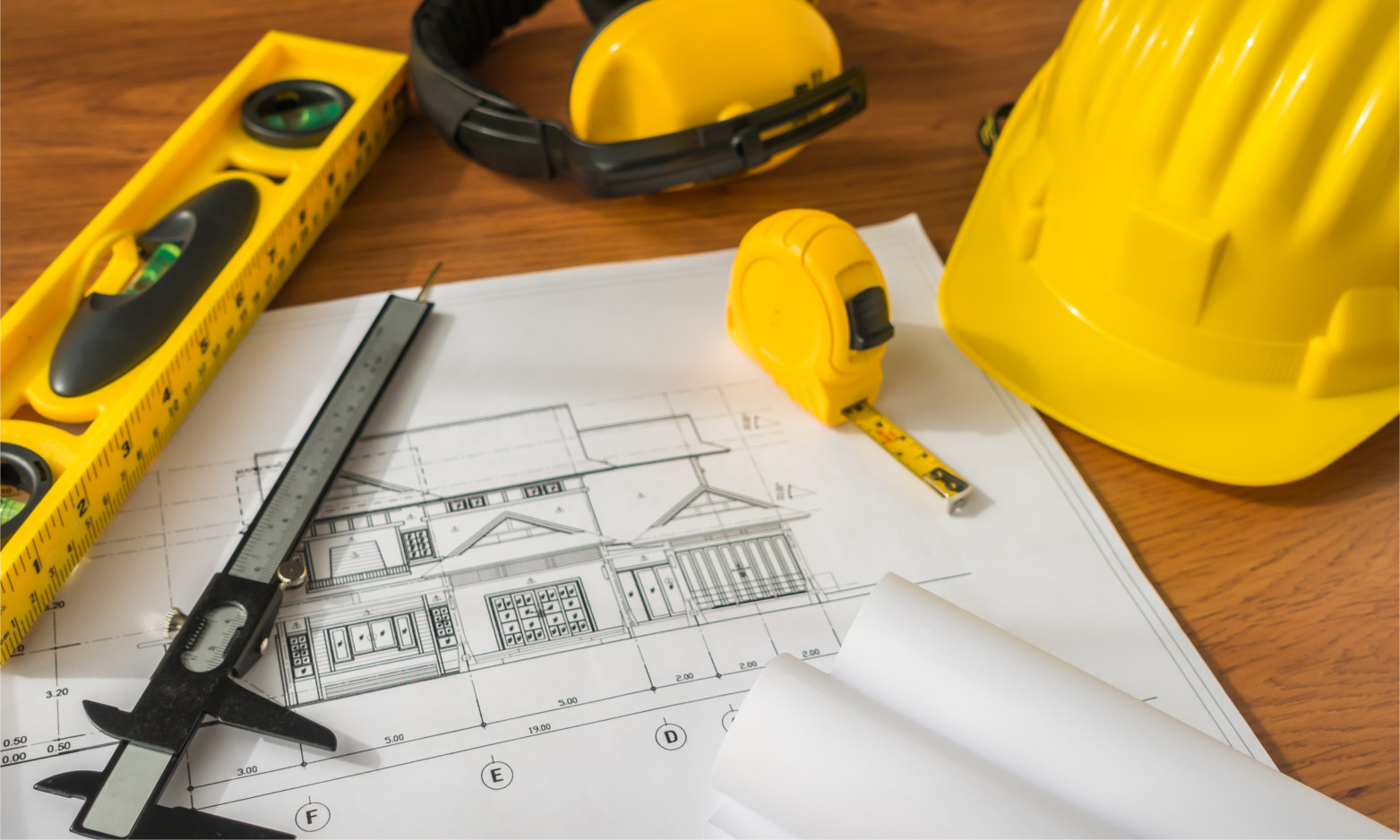 Construction plans with yellow helmet and drawing tools on bluep